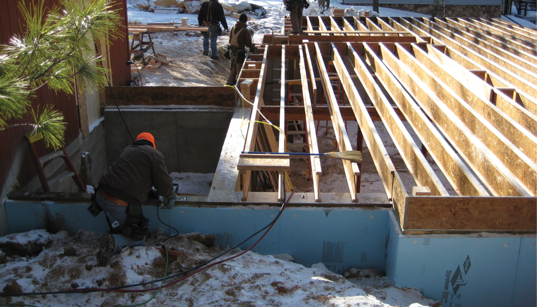 Builder preparing a foundation to receive the post and beam frame